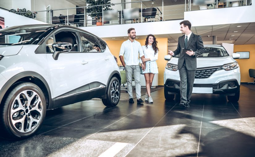Sales manager helping young couple to choose a new car